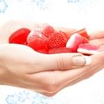 Hands full of red bonbons — Stock Photo