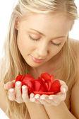 Bella bionda in spa con petali di rosa rosse — Foto Stock