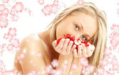 Lovely blond in spa with red and white petals and flowers — Stock Photo