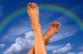 Piernas sobre cielo con nubes y arco iris — Foto de Stock