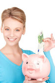 Lovely woman with piggy bank and money — Stockfoto