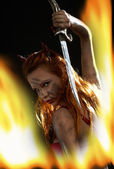 Dark devil girl with a knife in fire — Stock Photo