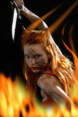 Red devil girl with a knife in fire — Stock Photo