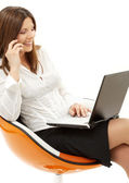 Businesswoman with laptop and phone in orange chair — Stockfoto