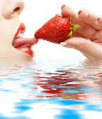 Strawberry, lips and tongue in water — Stock Photo
