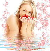 Blond with red and white rose petals and flowers in water — Stock Photo