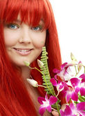 Lovely redhead with orchid — Stock Photo