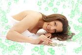 Szczęśliwy brunetka w spa z kwiatami — Zdjęcie stockowe