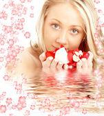 Felice biondo in acqua con fiori bianchi e rossi — Foto Stock