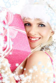Santa helper girl with pink gift box and snowflakes — Stock Photo