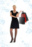 Elegant blond with shopping bags and snowflakes — Stock Photo