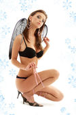 Black lingerie angel on high heels with snowflakes — Stock Photo