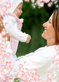 Happy mother with baby and flowers — Stock Photo