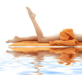 Long legs of relaxed lady with orange towel on white sand — Stock Photo