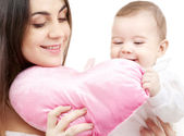 Baby and mama with heart-shaped pillow — Stock Photo