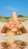 Tanning woman on sand — Stock Photo