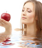 Woman with red apple in water — Stock Photo