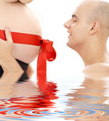 Proud father and belly with red ribbon in water — Stock Photo
