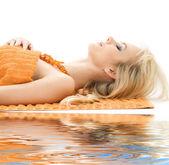 Beautiful lady with orange towels — Stock Photo