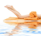 Long legs of relaxed lady with orange towel — Stock Photo