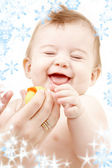 Laughing baby boy in mother hands with rubber duck — Stock Photo