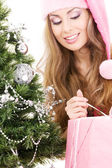 Santa helper girl with gift box and christmas tree — Stock Photo