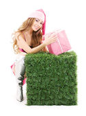 Santa helper with gift box and green cube — Stock Photo