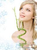 Blue-eyed blonde with bamboo in water — Stock Photo