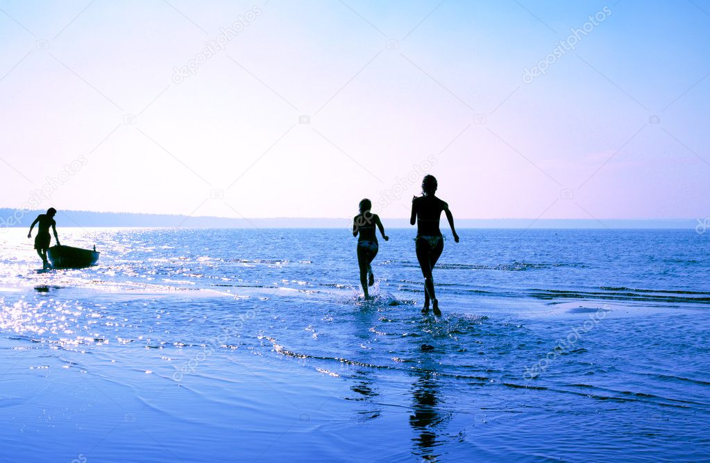 Silhouette image of two running girls and muscular man in water — Stock Photo #11761145