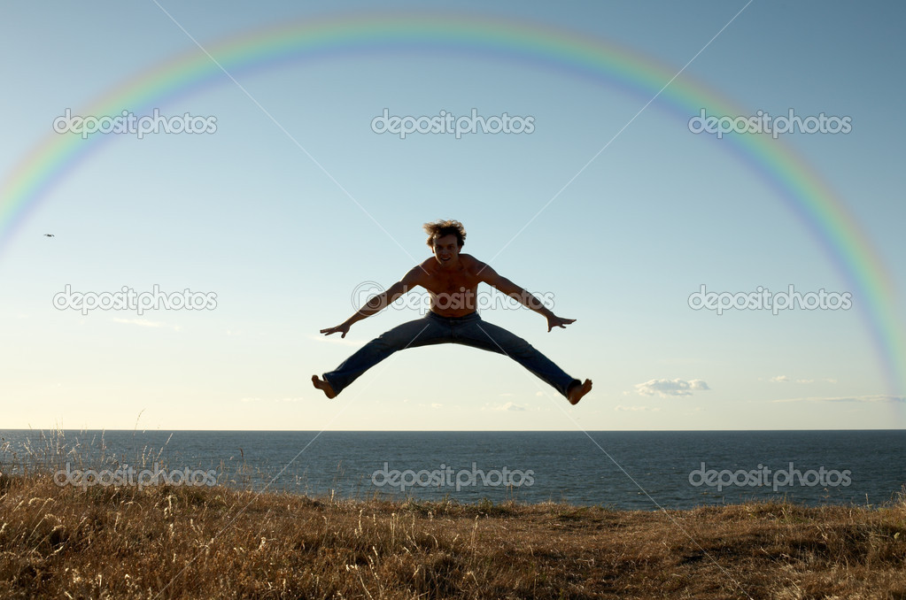Sporty man jumping under big colorful rainbow — Stock Photo #11763612