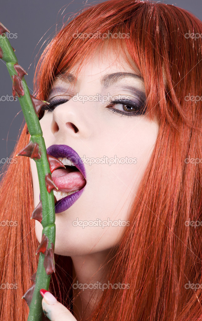 Closeup portrait of redhead woman licking sharp torns  Stock Photo #11769405