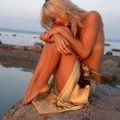 Sad topless girl on the rock - Stockfoto
