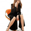 Businesswoman with phone in orange chair — Stock Photo