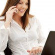 Businesswoman in chair with laptop and phone — Stock Photo