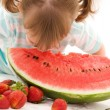 Little girl with strawberry and watermelon — Stock Photo #11773880