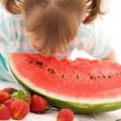 Little girl with strawberry and watermelon — Stock Photo