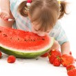 Little girl with strawberry and watermelon — Stock Photo #11774017