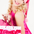 Cheerful santa helper girl with shopping bags - Stock Photo
