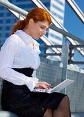Feliz empresaria con el portátil en la ciudad — Foto de Stock