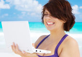 Woman with laptop computer on the beach — Stock Photo