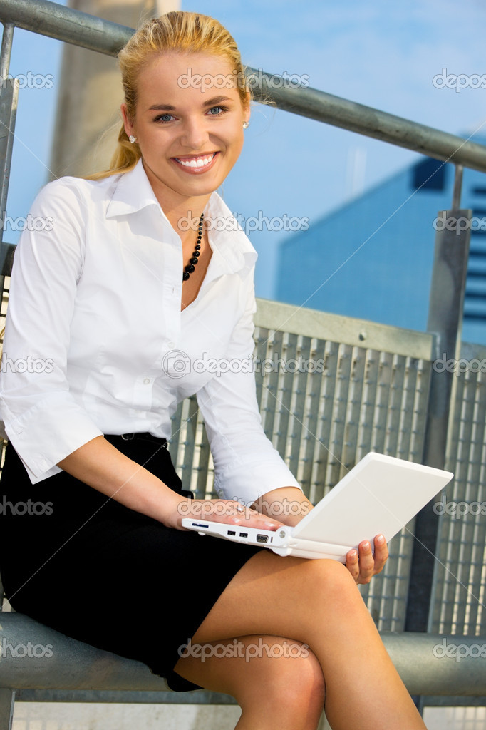 Happy businesswoman with laptop computer in the city — Stockfoto #11771878