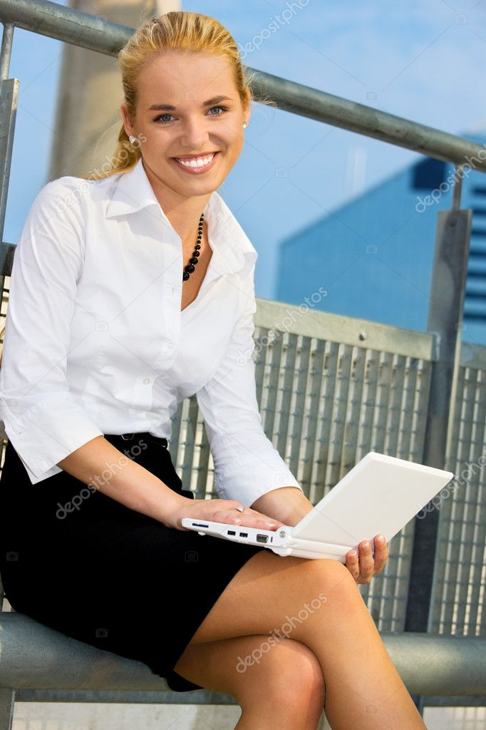 Happy businesswoman with laptop computer in the city — 图库照片 #11771878