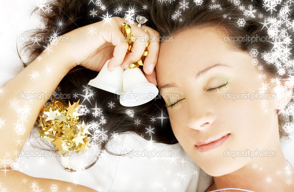 Picture of dreaming girl with christmas bells surrounded by rendered snowflakes — Stock Photo #11776509