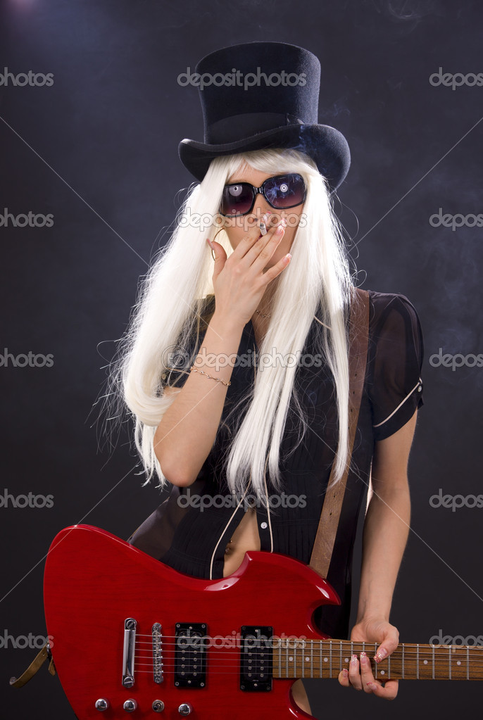 Woman in top hat with red electric guitar and cigarette — Stock Photo #11776514