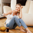Smiling teenage girl with remote control - Stock Photo