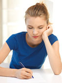 Pensive teenage girl with pen and paper — Stock Photo