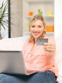 Femme heureuse avec ordinateur portable et de carte de crédit — Photo