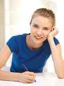 Happy teenage girl with pen and paper — Stock Photo