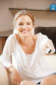 Happy teenage girl with TV remote — Stock Photo