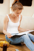 Calm and serious teenage girl with magazine — Stock Photo
